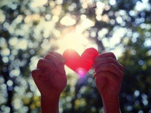 Image of two hands holding up a cutout paper heart to catch the sunlight outside