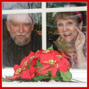 Picture of Patricia and her husband Les looking out a window decorated for Christmas