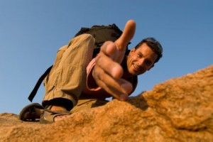 Picture of a man holding out his hand to help someone climb up a mountain.