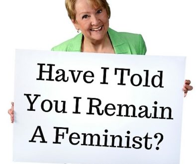 Patricia Morgan holding a sign, Have I Told You I Remain a Feminist?