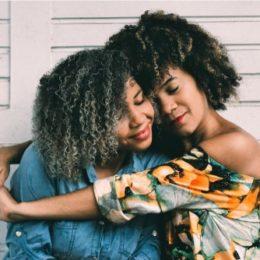 two women hug while saying kind words
