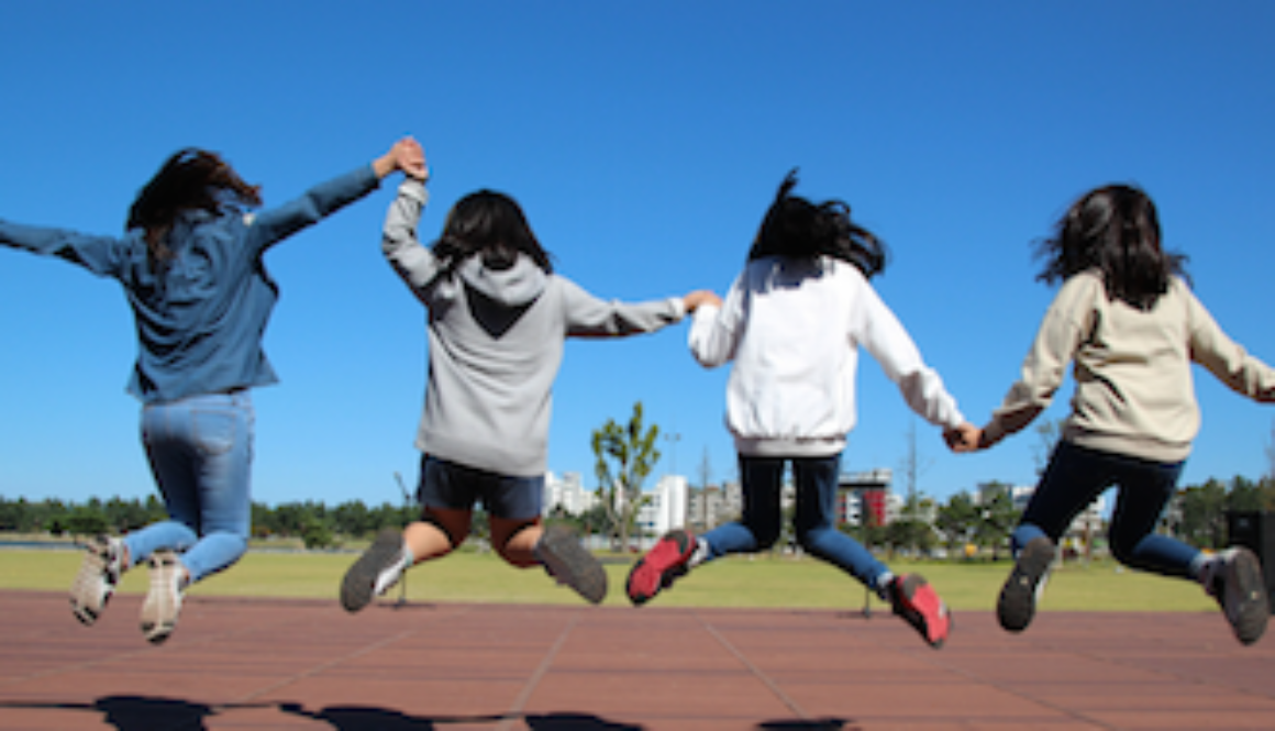 four youth jumping for joy